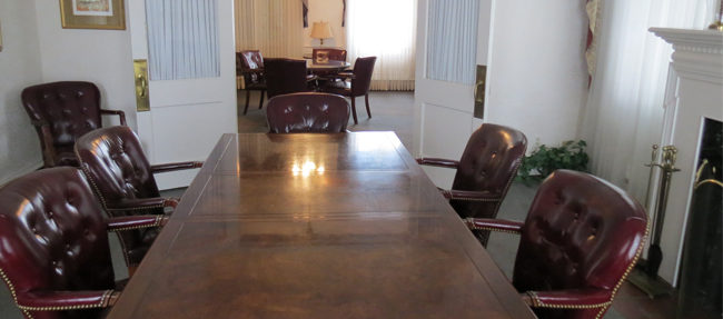 The Stouts also donated this striking mahogany board room table and 13 Chippendale-style chairs to the Foundation. Beyond the table, the music room is visible.
